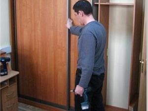 сборщик регулирует двери шкафа купе